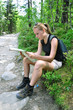 woman in trekking shoes reading map in the forrest, mountains