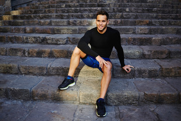 Charming athlete sitting on the stairs resting after jogging