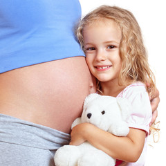 Little girl embracing belly of her pregnant mother