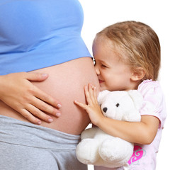 Little girl kissing her pregnant mother belly
