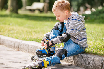Little boy lace his roller skate sitting on the sidewalk