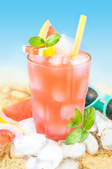 Cold grapefruit juice with ice on beach background
