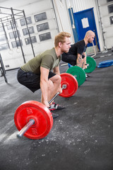 Two men train deadlift at crossfit center