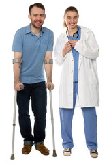 Man using crutches, next to a friendly physician