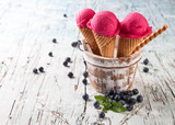 Fototapeta Blueberry fresh ice cream scoops in cones on wood