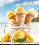 Lemon cce cream scoops in cones with blur beach