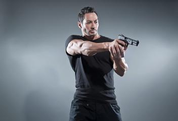 Action hero muscled man shooting with gun. Wearing black t-shirt