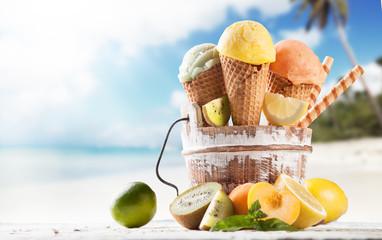 Fruit ice cream scoops in cones with blur beach