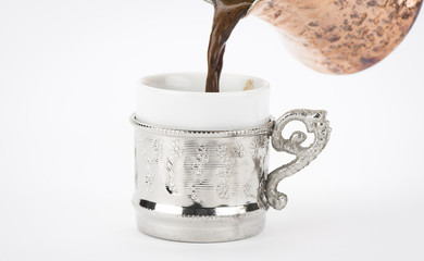 Pouring Turkish coffee in cup over white background