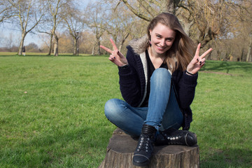 Woman sitting holding up peace signs