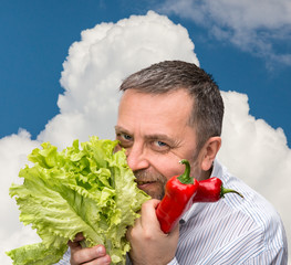 Man holding lettuce against the blue sky