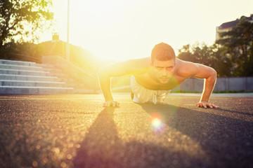 Young fit shirtless man doing push-ups outdoors