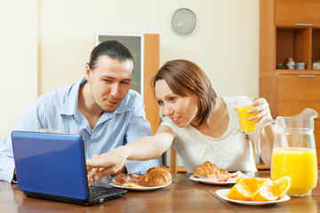 couple looking e-mail during breakfast
