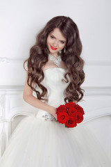 Beautiful bride girl with red roses bouquet posing in modern int