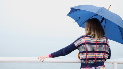 Back of woman with umbrella relaxing on the pier. Sea.