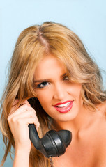 sexy woman smiling while using a vintage telephone