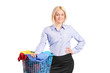 Woman standing by a laundry basket full of clothes