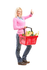 Young girl holding a shopping basket full of groceries