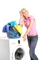 Bored woman standing by a washing machine