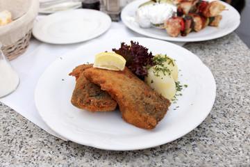 Fried carp with potatoes and slice of lemon