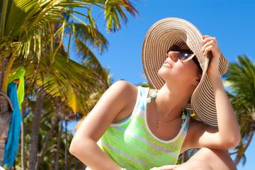 Woman under palm tree at beach