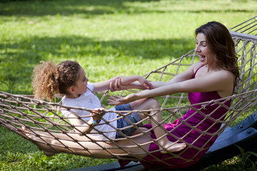 Mother and daughter are enjoying on hammock at park