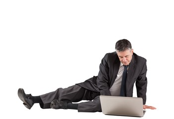 Concentrating businessman lying on floor using laptop