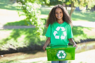 Young environmental activist smiling at the camera holding box