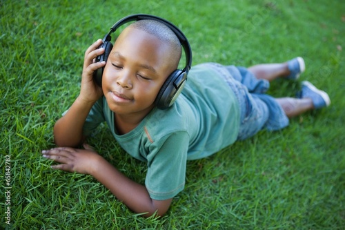 Little boy lying on grass listening to music with eyes closed