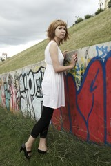 Attractive young woman against a wall of graffiti