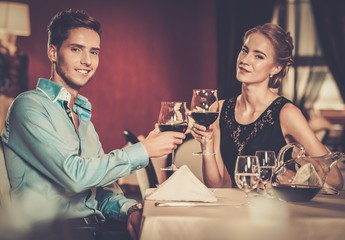 Beautiful young couple with glasses of wine in restaurant