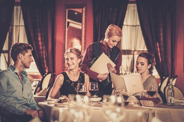 Friends with menus choosing in a luxury restaurant