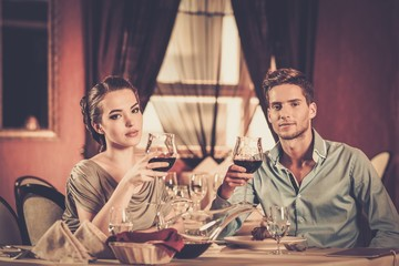 Young couple with glasses of wine in restaurant