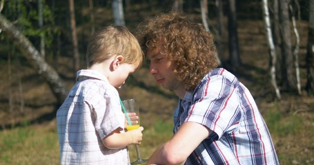 young father and gis son drinking juice outdoors