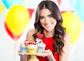 Beautiful woman holding cute party cupcakes