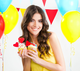 Beautiful woman holding two cupcakes