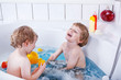 Two little twins boys having fun with water by taking bath in ba