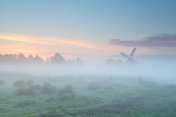 windmill silhouette in dense morning fog