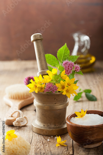 mortar with flowers and herbs for spa and aromatherapy