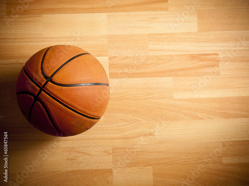 An official orange ball on a hardwood basketball court - 65847564