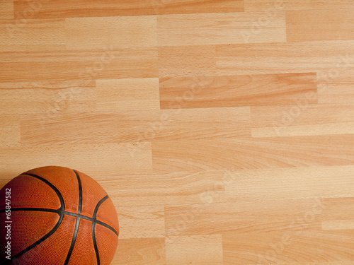 Poster An official orange ball on a hardwood basketball court