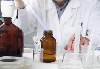 Laboratory assistant pours liquid from a bottle