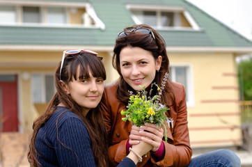 Two Beautiful Ladies Holding Flowers