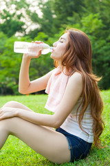Woman sitting tired and drinking water after exercise.