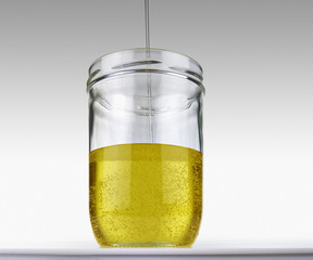 Olive oil flowing into glass jar