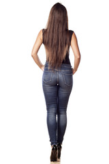 rear view pretty young woman in jeans posing on a white