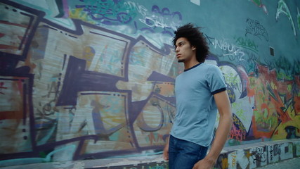 young, handsome man walking along the wall