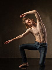 Young and stylish modern dancer on grey background