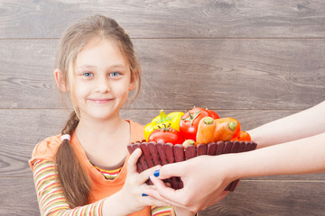 little girl takes hands basket with vegetables