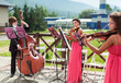 Girl violinist and bassist guy play outdoors